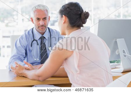 Patient explaining her painful to doctor in the office