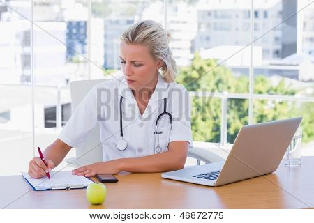 Blonde nurse writing on a notepad on her desk in her office