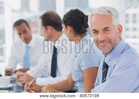 Smiling businessman posing in the meeting room with colleagues working next to him