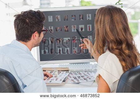 Editor de foto señalando el ordenador mientras se trabaja en equipo con un colega