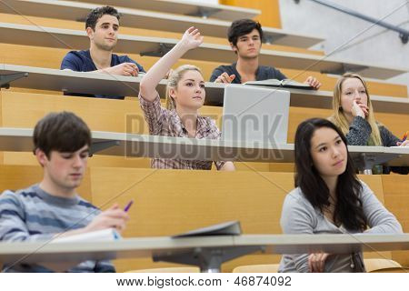 Students taking an active part in a lesson while sitting in a lecture hall