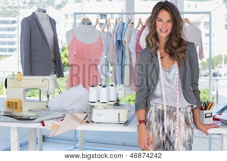 Fashion designer smiling and standing in a bright creative office