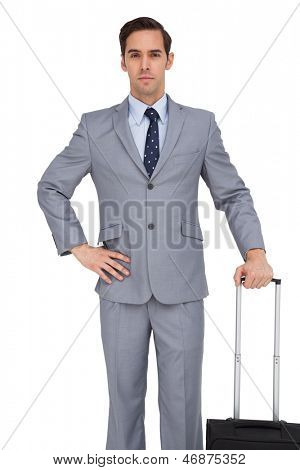 Businessman waiting while holding his suitcase on white background