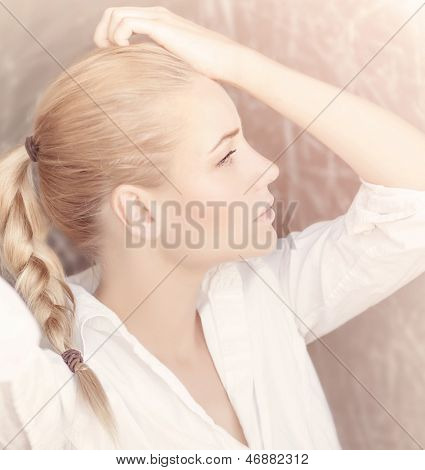 Closeup portrait of seductive woman isolated on tender pink background, profile of cute blond girl with pigtail hairstyle, beauty concept