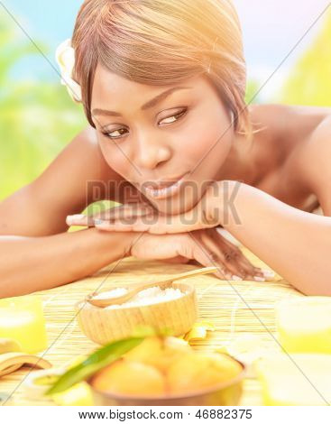 Attractive black woman relaxed on luxury spa resort, lying down on massage table with frangipani flower in hair on the beach in sunny day, healthcare concept