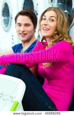 People in a launderette, washing their dirty laundry, sitting in front of washing machines and talking together