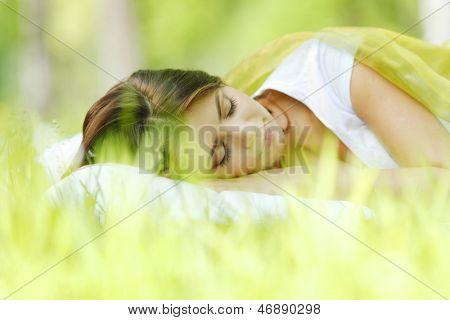 Joven mujer durmiendo sobre una almohada suave en la hierba fresca del resorte