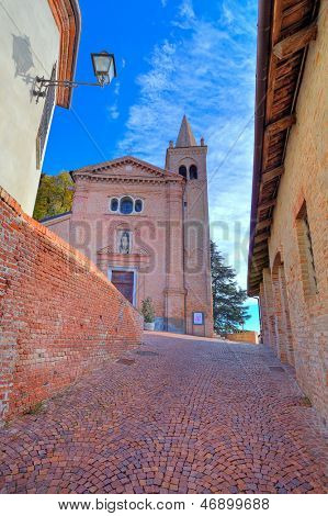 Vertical image of  red brick church and narrow cobblestone street in at medieval part of the town in Monticello D'Alba, Italy.
