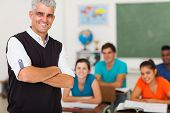 stock photo of middle class  - smiling middle aged high school teacher with arms folded standing in front of the class - JPG
