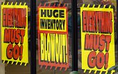 image of going out business sale  - signs promote a giant sale as a store clears inventory before the location closes for business - JPG