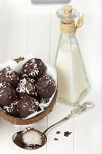 picture of bittersweet  - With bittersweet chocolate covered coconut milk rice truffles in a coconut shell and a bottle of coconut cream on a wooden tray - JPG