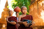 stock photo of southeast asian  - Young Buddhist monks walking morning alms in Old Bagan - JPG