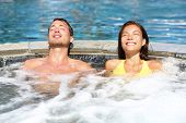 stock photo of hot-tub  - Spa couple relaxing enjoying jacuzzi hot tub bubble bath outdoors on romantic summer vacation travel holidays or honeymoon - JPG