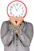 Formally dressed man holding a clock in place of his face with his hands chained with a metallic cha