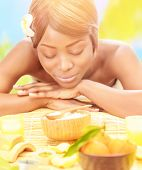 Attractive black woman relaxed on luxury spa resort, lying down on massage table with closed eyes on