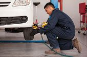 stock photo of suspenders  - Young mechanic using an air gun to tighten a tire bolts on a suspended car at an auto shop - JPG