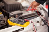 stock photo of  multimeter  - Closeup of the hands of a mechanic checking a car battery at an auto shop - JPG