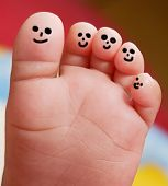 foto of painted toes  - Nice foot of a baby with smiley faces painted toes - JPG