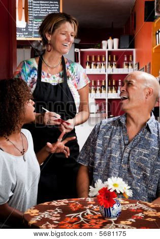Woman Taking Order From Couple In Coffee House
