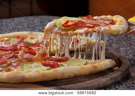 Italian Pizza slice with melted cheese on a wooden dish