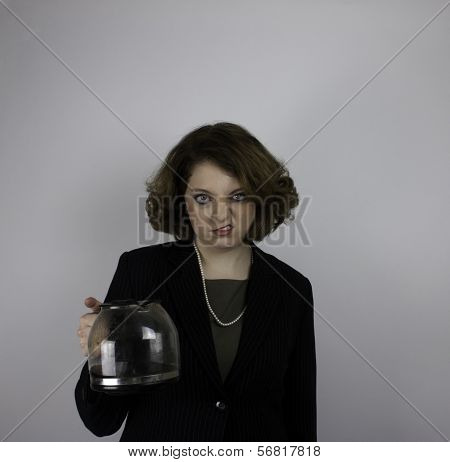 Young business woman snarling as she holds coffee pot