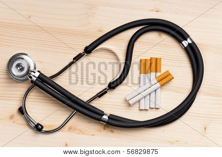Close up stethoscope and cigarette against wooden surface