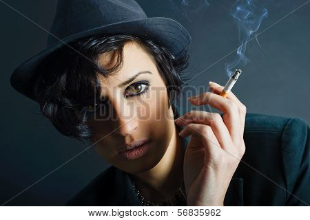 Brunette Woman Smoking A Cigarette On Black Background Wearing A Hat