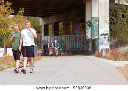 Young Couple Walks And Eats Popsicles In Urban Setting