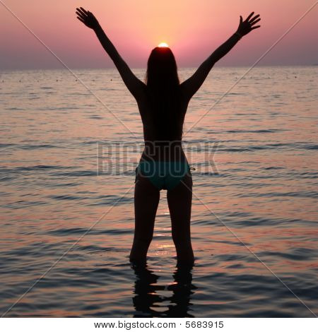 Freedom - girl in a sea at sunset