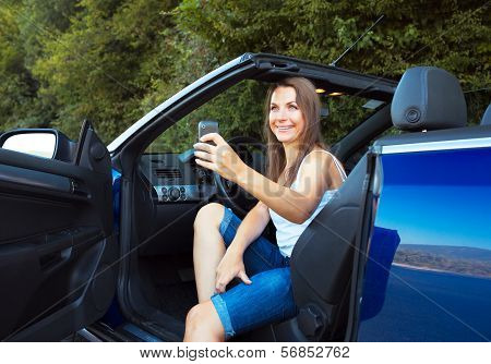 Smiling Caucasian Woman With Cellphone In A Car