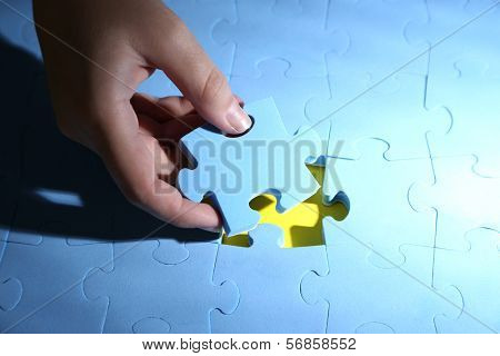 Hand holding puzzle piece, close up