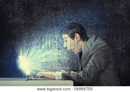 Young man in suit looking astonished in laptop. Surfing the internet