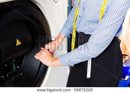 Female cleaner in laundry shop using cleaning machine for dry-cleaning