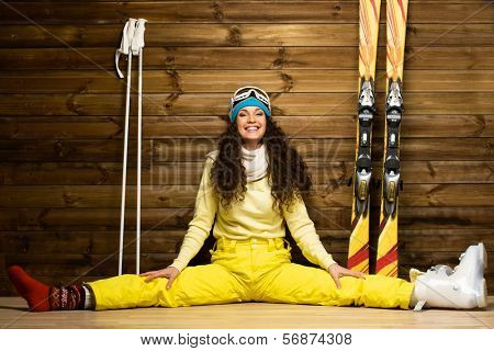 Happy woman with skis and ski boots sitting on a floor near wooden wall