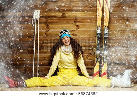 Happy woman with skis and ski boots sitting near wooden wall in snowflakes