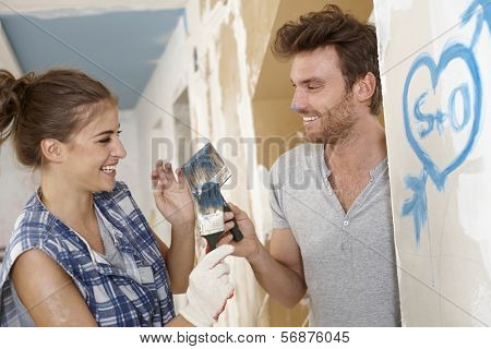 Loving couple having fun at home renovation, painting, DIY.