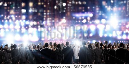 Crowd of businesspeople standing with back with lights at background