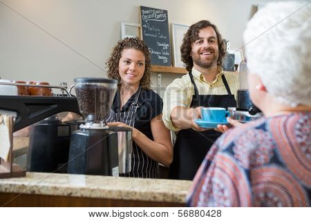 Smiling cafe owners serving coffee to senior woman at counter