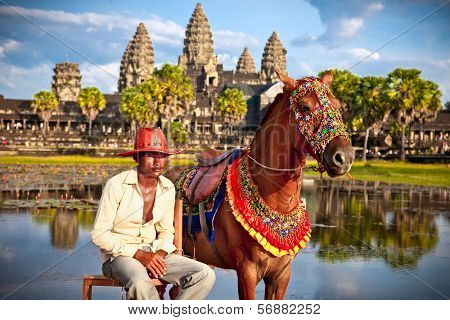 ANGKOR WAT, CAMBODIA - NOV  20,2013: Unidentified man and horse for rent in Angkor Wat conplex on Nov 20, 2013, Cambodia. Angkor temples and ruins are UNESCO World Heritage Site.