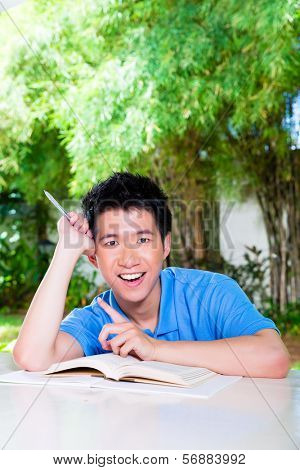 Young Chinese Asian student is successful at home with difficult homework assignment for school next day