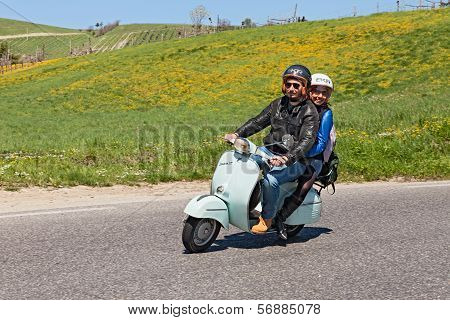 Couple Riding A Vintage Scooter