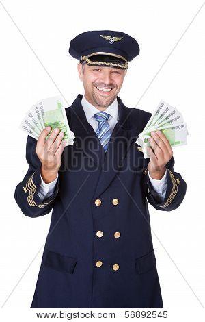 Portrait Of Happy Pilot Holding Euros