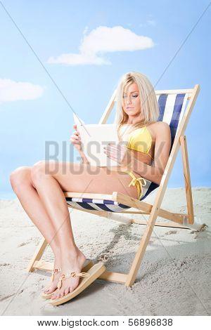 Beautiful Young Woman In Bikini Reading A Book