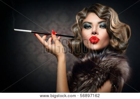 Beauty Retro Woman with Mouthpiece. Vintage Styled Beautiful Lady with cigarette. Smoking Model Girl Portrait. Hairstyle and Make up