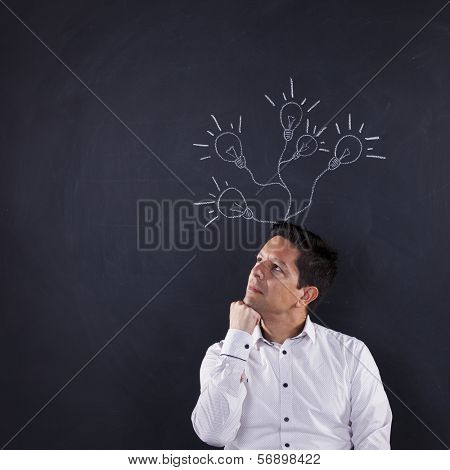 Happy man and light bulbs sketched on blackboard, growing from her head