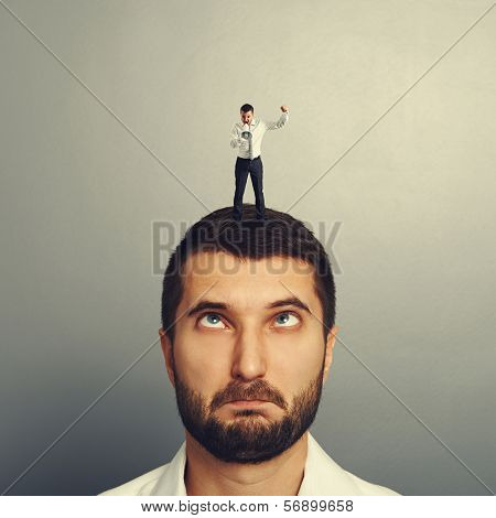 small boss standing on the head and screaming at foolish worker