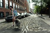stock photo of tram  - Young brunette girl holding dog at historical old tram rails at Dumbo area in Brooklyn NY - JPG