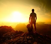 foto of breathtaking  - Hiker standing with backpack on top of a mountain and enjoying sunrise - JPG