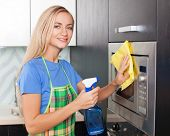 Woman cleaning microwave at kitchen. Female doing housework