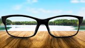 image of distort  - Clear lake in glasses on the background of blurred nature - JPG